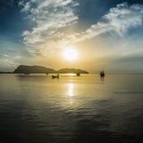 放置在海的波浪表面的传统小船有一朵长的大山、美好的日出和云彩的在一个早晨 免版税库存照片