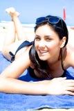放置在海滩微笑的愉快的女孩 免版税库存照片