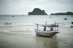 放置在海滩的传统渔船在有山和海岛的,选择聚焦,被过滤的图象海附近 免版税库存照片