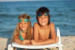 放置在海滩睡椅佩带的游泳风镜的孩子 免版税库存照片