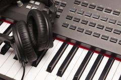 放置在电子合成器键盘的听的耳机 免版税库存图片