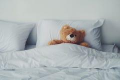 放置在白色床的熊玩偶 免版税库存照片