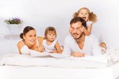 放置在睡衣的白色床的微笑的家庭 图库摄影