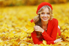 放置在秋叶的妇女 免版税库存照片