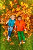 放置在秋叶的愉快的男孩 免版税库存图片