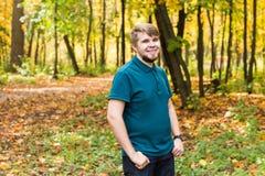 放置在秋天公园的年轻微笑的人画象 库存照片