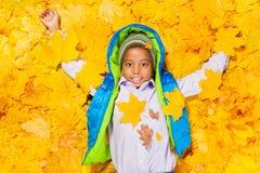 放置在秋天槭树叶子的非洲男孩 图库摄影