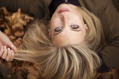 放置在秋天的一名美丽的白肤金发的妇女的特写镜头离开 免版税库存照片