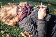 放置在秋季公园和使用巧妙的电话的女孩 免版税库存图片