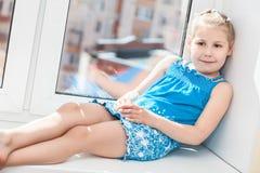 放置在窗口的蓝色礼服的Jouful女孩 库存照片