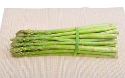 放置在竹子的新鲜的绿色芦笋新芽 图库摄影
