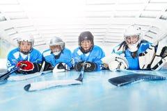 放置在线的滑冰场的年轻曲棍球运动员 免版税图库摄影