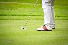 放置在绿色的男性高尔夫球运动员的英尺 图库摄影