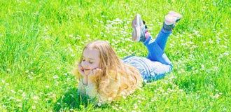 放置在绿草的孩子女孩在春天 和平和平静的概念 笑容的女孩花费休闲户外 免版税图库摄影