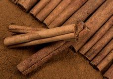 放置在肉桂粉上面的肉桂条用三根棍子  免版税库存照片