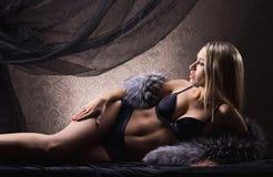 放置在色情女用贴身内衣裤和毛皮的一名性感的白肤金发的妇女 库存照片