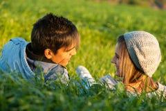 放置在草地的夫妇在日落。 库存图片