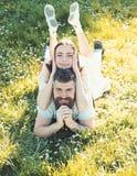 放置在草春日的男人和妇女 春天休闲概念 在放置在草甸,自然的愉快的笑容的夫妇 库存图片