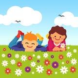 放置在草甸领域草的愉快的孩子 免版税库存照片