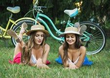 放置在草的两个女孩特写镜头在一顿野餐在公园 免版税库存图片