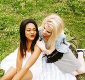 放置在草的两个年轻俏丽的少年女孩最好的朋友做获得selfie的照片乐趣,生活方式愉快的人民 免版税库存照片