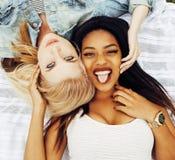 放置在草的两个年轻俏丽的少年女孩最好的朋友做获得selfie的照片乐趣,生活方式愉快的人民 免版税图库摄影