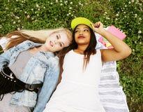 放置在草的两个年轻俏丽的少年女孩最好的朋友做获得selfie的照片乐趣,生活方式愉快的人民 免版税库存图片