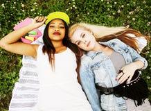 放置在草的两个年轻俏丽的少年女孩最好的朋友做获得selfie的照片乐趣,生活方式愉快的人民 库存图片