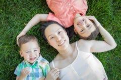 放置在草的中国母亲和混合的族种孩子 库存照片