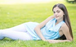 放置在草的妇女室外 免版税库存图片