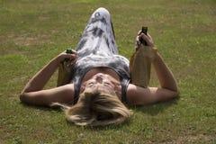 放置在草的妇女抓住啤酒瓶 免版税图库摄影