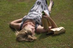 放置在草的妇女抓住啤酒瓶 免版税库存图片