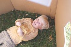 放置在草的幼儿,当使用在纸板箱堡垒时 免版税库存图片