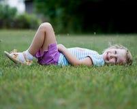 放置在草的愉快的小女孩 库存图片