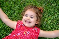 放置在草的愉快的微笑的小小孩女孩在有红色礼服的公园 库存照片