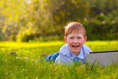 放置在草的笑的男孩在公园 免版税库存图片