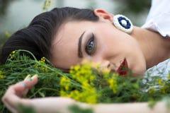 放置在草的美丽的妇女 免版税库存照片