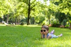 放置在草的逗人喜爱的矮小的小孩女孩在一个晴朗的夏天 免版税图库摄影
