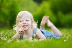 放置在草的逗人喜爱的矮小的小孩女孩 免版税库存照片