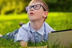放置在草的滑稽的男孩在有膝上型计算机的公园 免版税库存图片