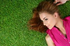 放置在草的年轻美丽的女孩在公园 库存照片