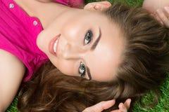 放置在草的年轻美丽的女孩在公园 免版税库存图片