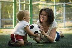 放置在草皮的腹部和使用与有足球的小儿子的年轻母亲在橄榄球场 妈妈和儿子一起获得乐趣 免版税库存照片