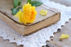 放置在葡萄酒书的黄色玫瑰在鞋带小垫布 免版税库存照片