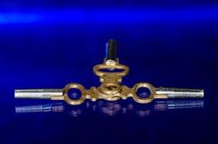 放置在蓝色表面的三把古色古香的黄铜怀表钥匙 库存照片