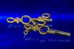 放置在蓝色表面的三把古色古香的黄铜怀表钥匙 图库摄影