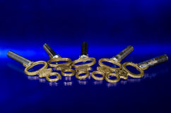 放置在蓝色表面的五把古色古香的黄铜怀表钥匙 免版税库存照片