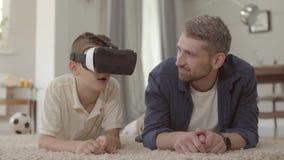 放置在蓬松地毯的地板的画象英俊的爸爸和儿子使用虚拟现实玻璃,愉快友好 股票录像