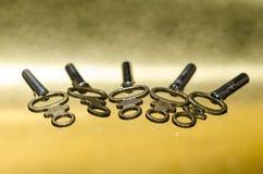 放置在金黄表面的五把古色古香的黄铜怀表钥匙 库存图片