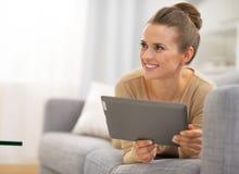 放置在长沙发和使用片剂个人计算机的妇女 库存照片